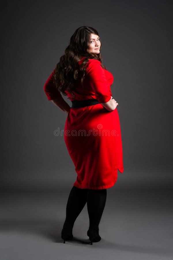 Modelo de forma positivo do tamanho no vestido vermelho, mulher gorda no fundo cinzento, corpo fêmea excesso de peso fotos de stock