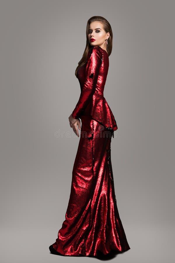 Modelo de forma Red Sparkling Dress, mulher elegante no vestido de nivelamento longo, retrato bonito da beleza da menina foto de stock royalty free