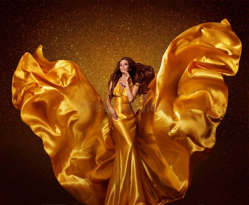 Modelo de forma Woman do ouro, asas de voo da tela de seda no vento fotografia de stock