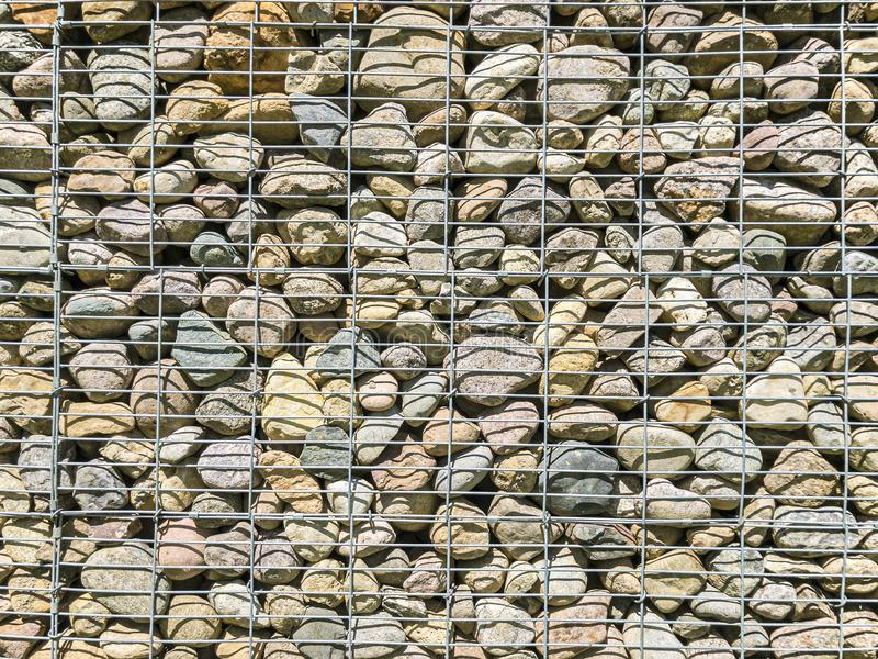 Modelo de Gabion rejilla del metal con muchas piedras naturales redondas dentro fotos de archivo libres de regalías
