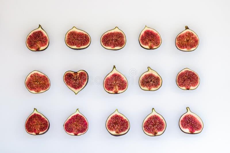 Modelo de higos maduros cortados bajo la forma de rectángulo con el corazón aislado en el fondo blanco Ejemplo de la fruta Alimen fotos de archivo libres de regalías