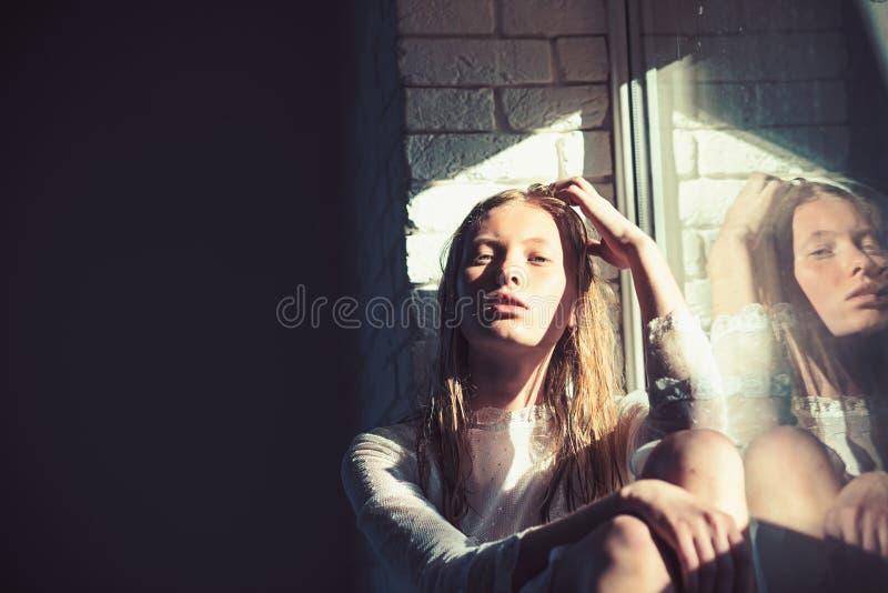 Modelo de la belleza con el pelo rubio mojado La mujer sensual se relaja en la ventana Mujer con la cara joven de la piel Muchach imágenes de archivo libres de regalías