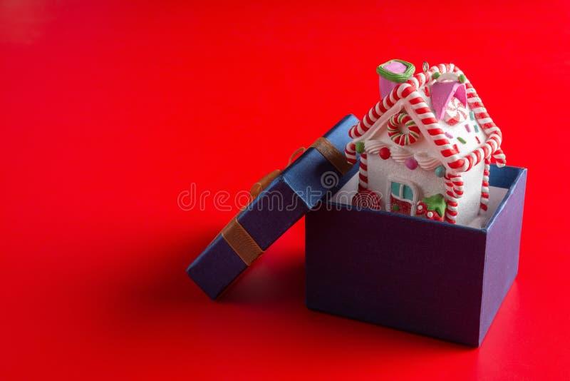 Modelo de la casa con la decoración de la Navidad dentro de una actual caja en rojo foto de archivo libre de regalías