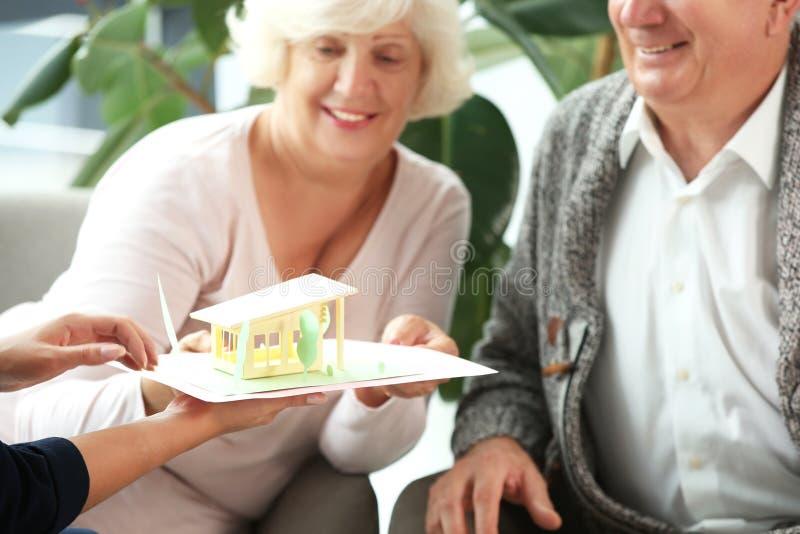 Modelo de la demostración del agente inmobiliario de la casa a los clientes en su oficina imagen de archivo libre de regalías