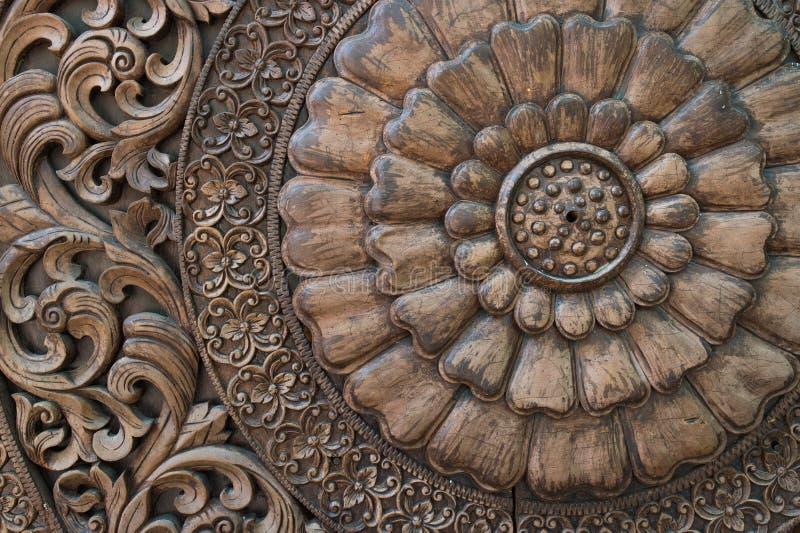 Modelo de la flor tallado en el fondo de madera imagen de archivo