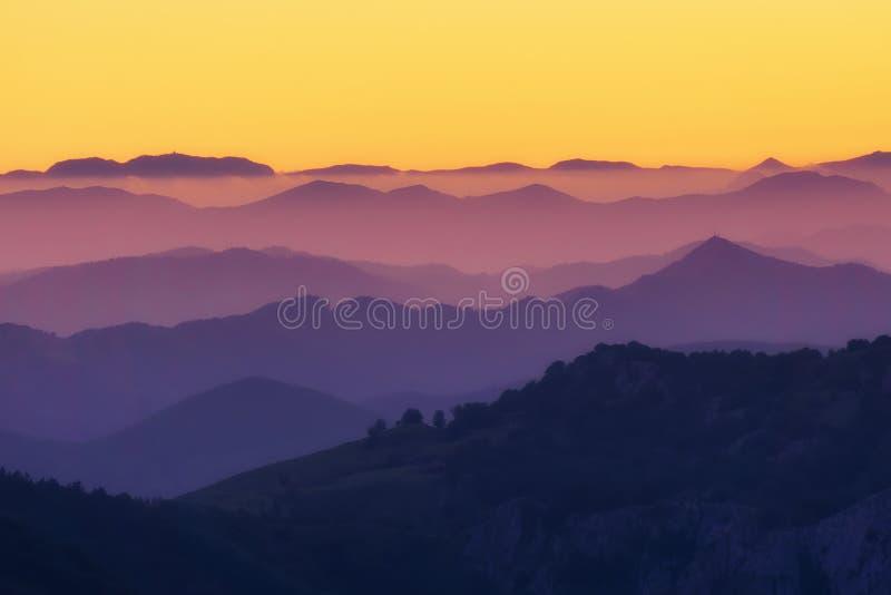 Modelo de las capas distantes de la montaña en la puesta del sol fotografía de archivo libre de regalías