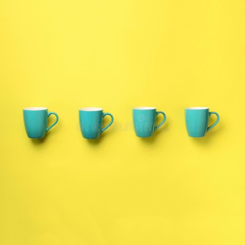 Modelo de las tazas azules sobre fondo amarillo Cosecha cuadrada Celebración de la fiesta de cumpleaños, concepto de la fiesta de foto de archivo libre de regalías