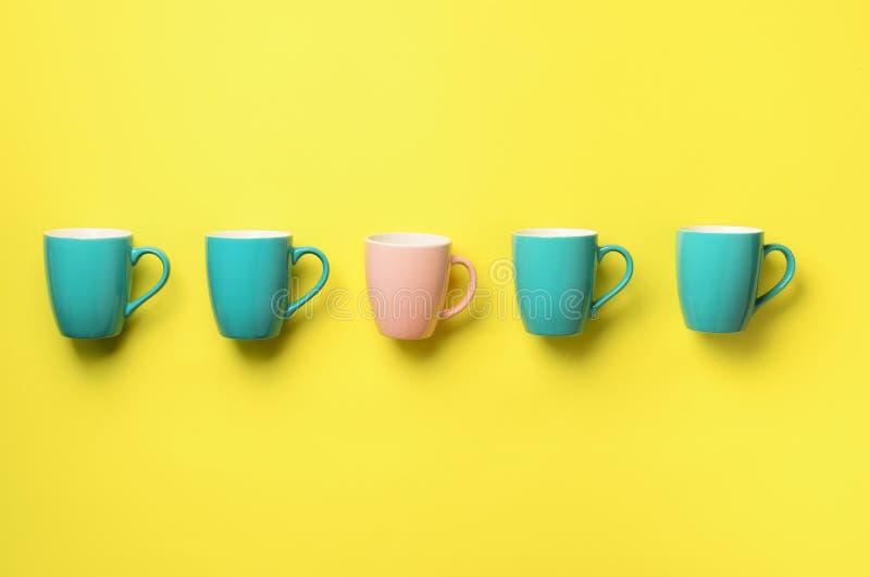 Modelo de las tazas azules y rosadas sobre fondo amarillo Celebración de la fiesta de cumpleaños, concepto de la fiesta de bienve fotografía de archivo libre de regalías