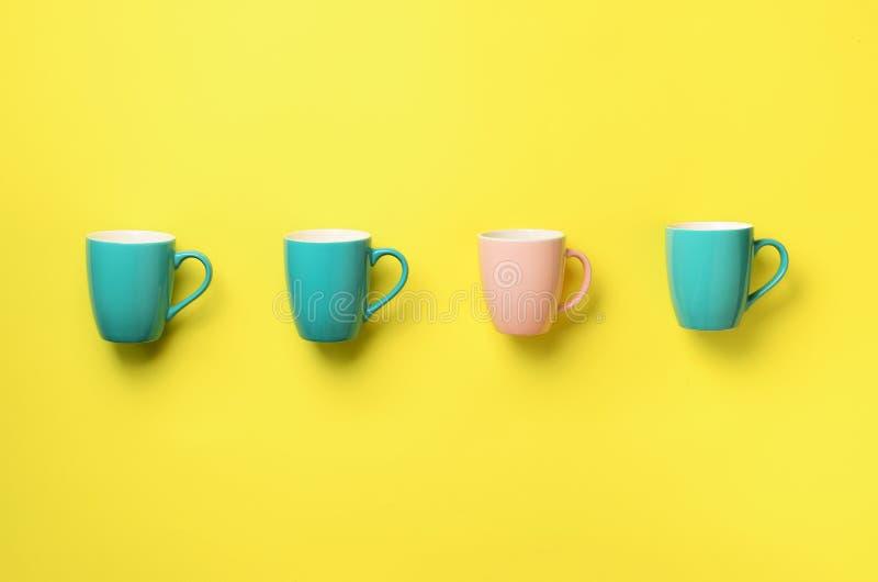 Modelo de las tazas azules y rosadas sobre fondo amarillo Celebración de la fiesta de cumpleaños, concepto de la fiesta de bienve imagen de archivo
