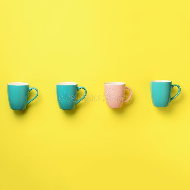 Modelo de las tazas azules y rosadas sobre fondo amarillo Cosecha cuadrada Celebración de la fiesta de cumpleaños, concepto de la fotografía de archivo