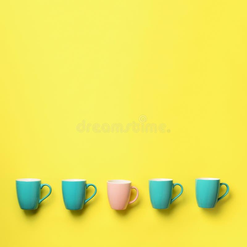 Modelo de las tazas azules y rosadas sobre fondo amarillo Cosecha cuadrada Celebración de la fiesta de cumpleaños, concepto de la imágenes de archivo libres de regalías