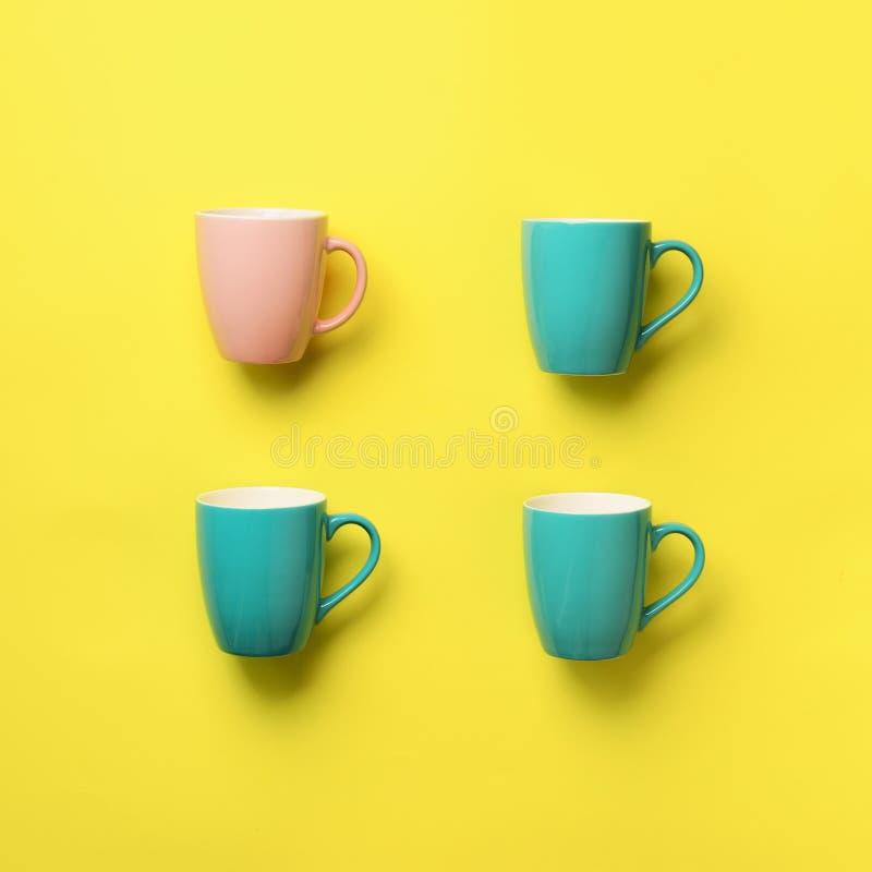 Modelo de las tazas azules y rosadas sobre fondo amarillo Cosecha cuadrada Celebración de la fiesta de cumpleaños, concepto de la fotos de archivo