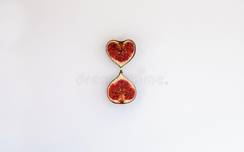 Modelo de los higos maduros cortados aislados con forma del corazón en el fondo blanco Ejemplo de la fruta Foto de la comida Ende fotografía de archivo