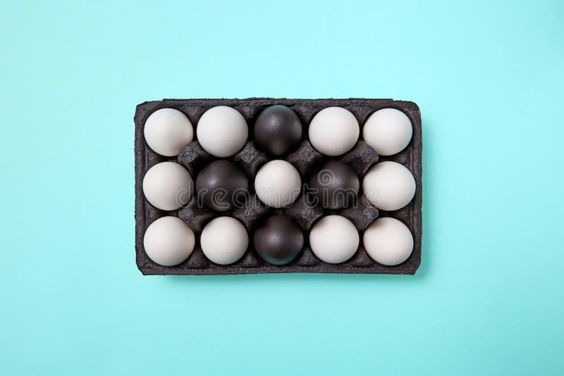 Modelo de los huevos negros blancos y pintados en una caja de cartón negra en un fondo azul con el espacio de la copia Semana San fotografía de archivo