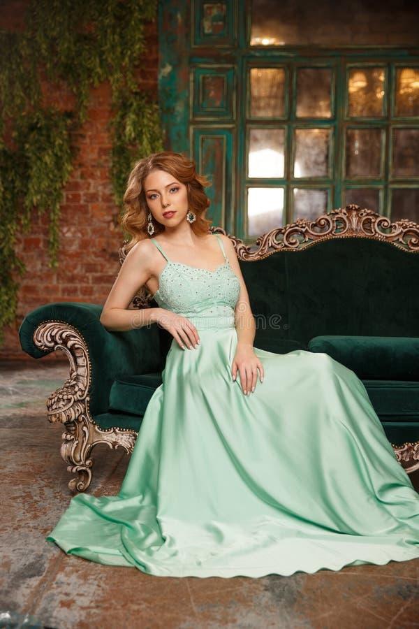 Modelo de lujo de la mujer en un vestido menta-coloreado que se sienta en un sofá del vintage Muchacha de la belleza con un maqui imágenes de archivo libres de regalías