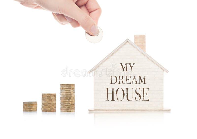 Modelo de madeira da casa com as moedas ao lado dele e da mão fotografia de stock royalty free