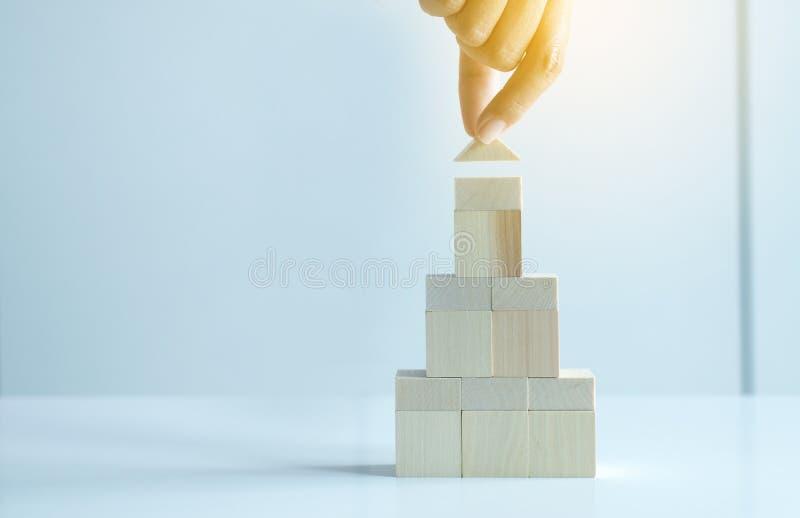 Modelo de madeira da casa da pilha do bloco da terra arrendada da mulher da mão no fundo branco, crescimento dos bens imobiliário foto de stock
