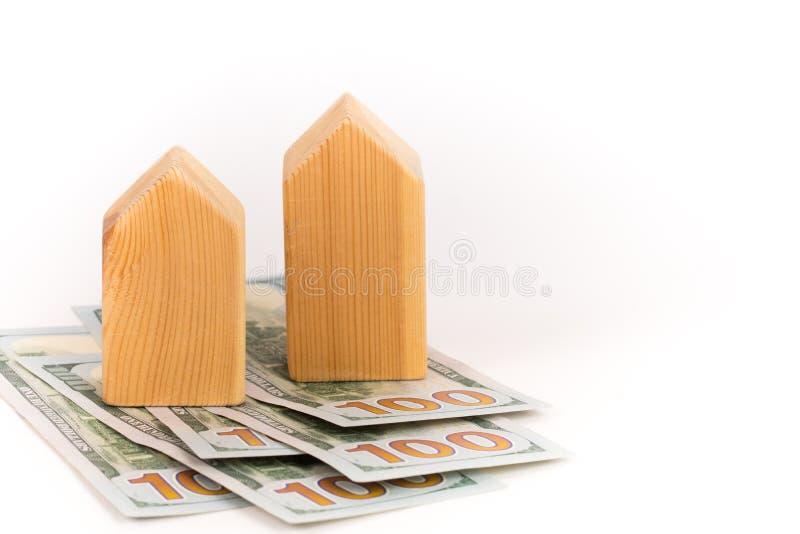 Modelo de madera con los billetes de banco de los dólares, concepto costado costoso de la casa de los bienes raices fotografía de archivo