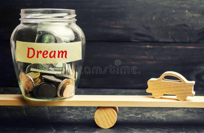 Modelo de madera del coche y un tarro de cristal con las monedas y la inscripción 'sueño 'en las escalas Acumulación de dinero pa foto de archivo