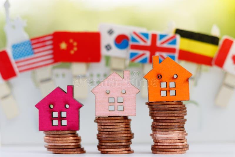 Modelo de madera de la casa en pila de las monedas Propiedad, finanzas, fotografía de archivo libre de regalías