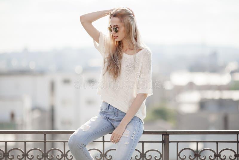 Modelo de manera en alineada de oro Mirada del verano Vaqueros, suéter, gafas de sol fotos de archivo libres de regalías