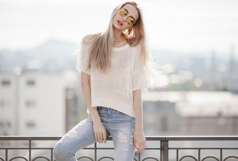 Modelo de manera en alineada de oro Mirada del verano Vaqueros, suéter, gafas de sol imágenes de archivo libres de regalías
