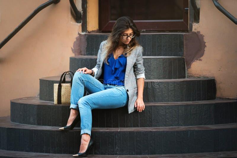 Modelo de manera en calle Mujer atractiva hermosa en la ropa de moda elegante de la caída que se sienta en las escaleras imagenes de archivo