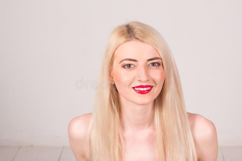 Modelo de manera que presenta en el estudio Mujer hermosa sonriente con el pelo rubio de largo recto, los dientes blancos, los la foto de archivo libre de regalías