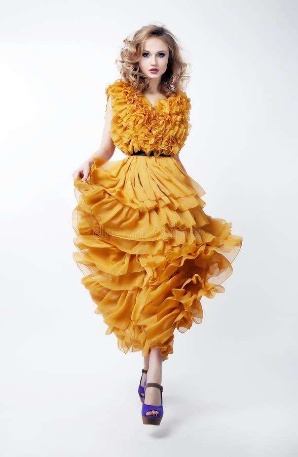 Modelo de manera rubio de la mujer encantadora en alineada amarilla imagen de archivo