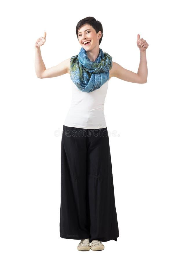 Modelo de moda alegre en pantalones de la ancho-pierna y bufanda colorida con los pulgares para arriba fotografía de archivo libre de regalías