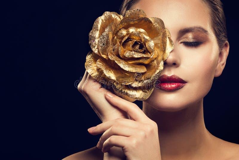 Modelo de moda Beauty Portrait con el oro Rose Flower, maquillaje de lujo de la mujer de oro Rose Jewelry fotos de archivo libres de regalías