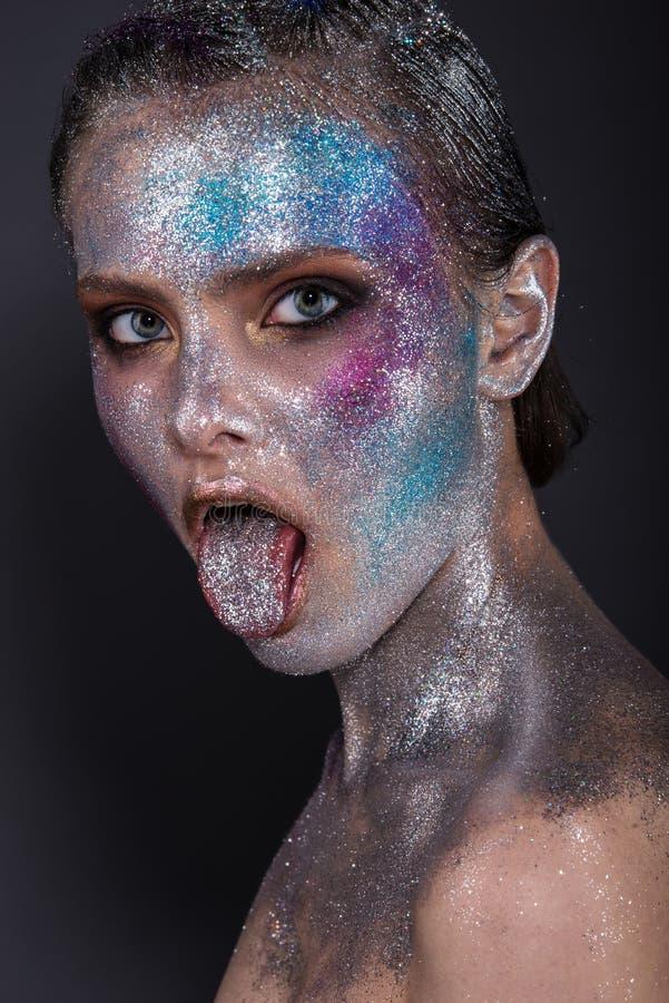 Modelo de moda con maquillaje brillante y brillo colorido y chispas en su cara y cuerpo foto de archivo