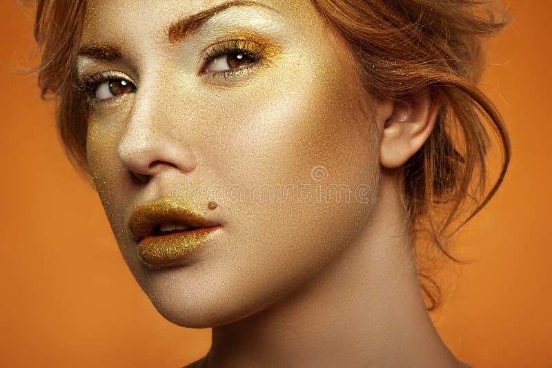 Modelo de moda con maquillaje de oro en cara y los labios foto de archivo
