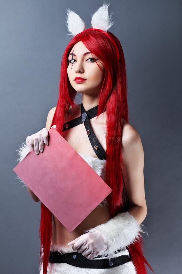 Modelo de moda de la belleza Girl con la peluca roja en el fondo gris, holdi foto de archivo