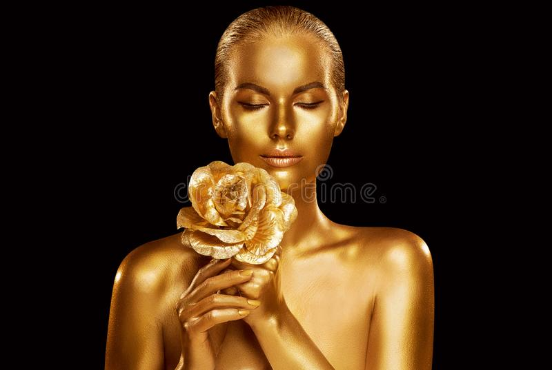 Modelo de moda del oro Beauty Portrait con Rose Flower, mujer de oro Art Luxury Makeup imagenes de archivo