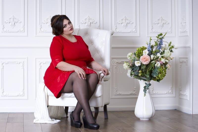 Modelo de moda del tamaño extra grande en el vestido de noche rojo, mujer gorda en interior de lujo, cuerpo femenino gordo, retra imagen de archivo