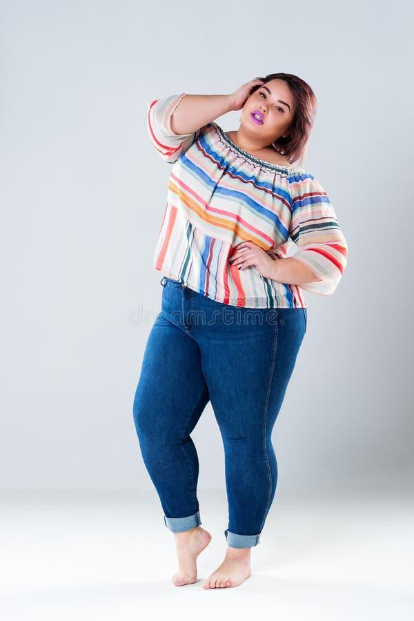 Modelo de moda del tamaño extra grande en ropa casual, mujer gorda en el fondo gris, concepto positivo del cuerpo imagen de archivo