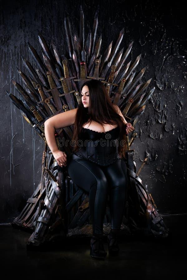 Modelo de moda del tamaño extra grande que se sienta en el trono del hierro fotos de archivo