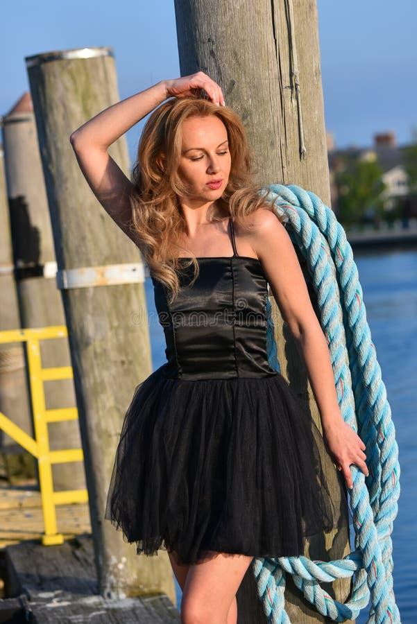 Modelo de moda elegante en el vestido negro que disfruta de la luz del sol que se coloca en el embarcadero en el puerto deportivo fotos de archivo