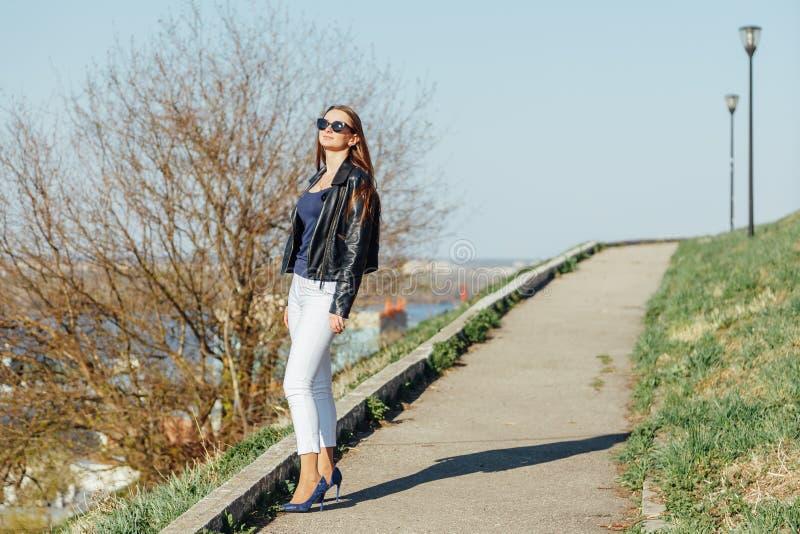 Modelo de moda en las gafas de sol y la presentaci?n negra de la chaqueta de cuero al aire libre imagenes de archivo
