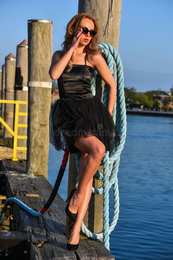 Modelo de moda en vestido negro y las gafas de sol que presentan en el embarcadero fotografía de archivo libre de regalías