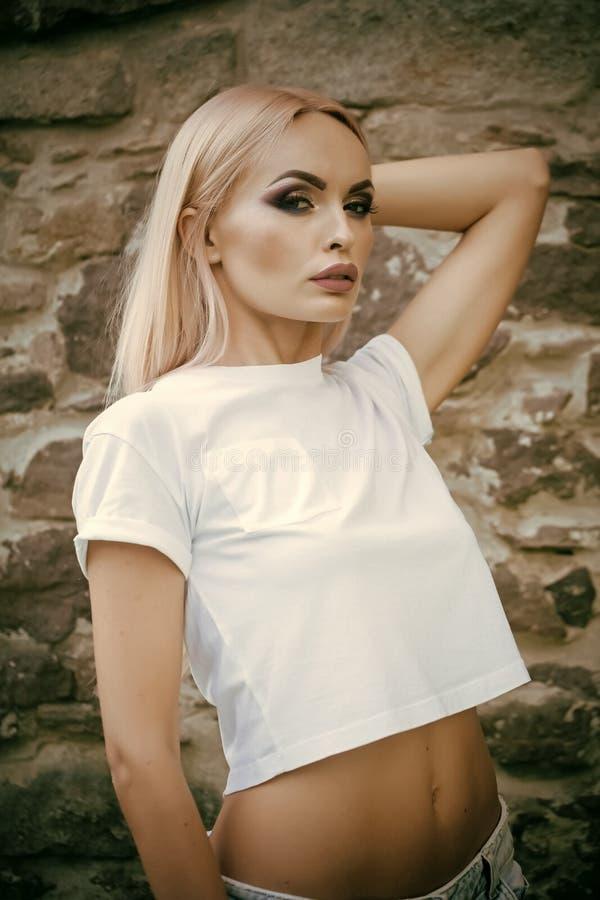 Modelo de moda, estilo, encanto Mujer con el vientre atractivo en la camiseta, moda Mujer sensual con el pelo rubio largo, cara d fotografía de archivo libre de regalías