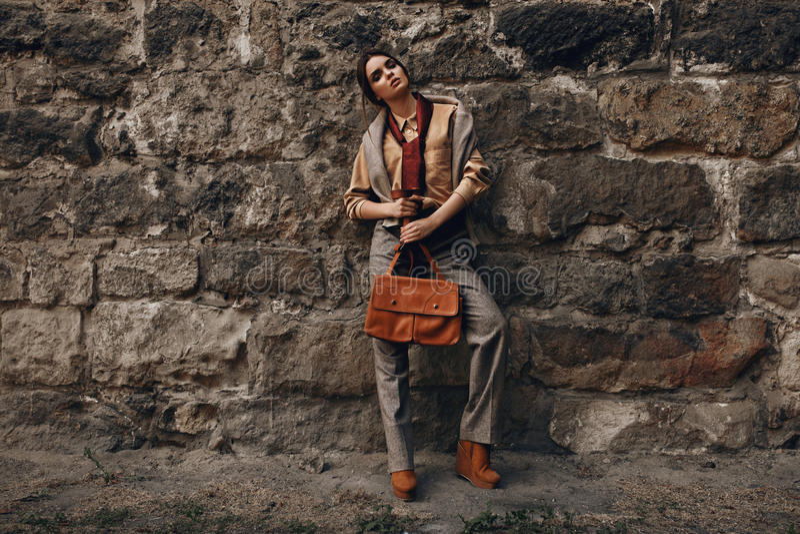 Modelo de moda In Fashionable Clothes Mujer hermosa cerca de la pared imagen de archivo libre de regalías