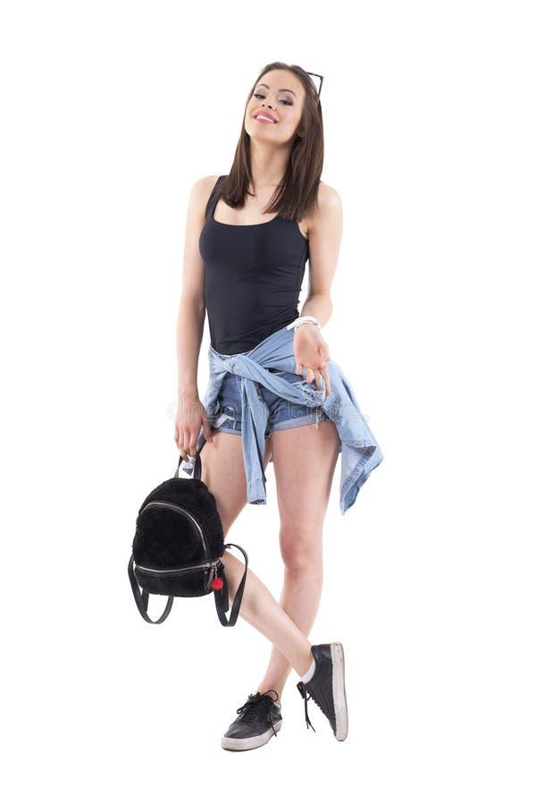 Modelo de moda feliz confiado de la mujer joven que presenta y que sonríe con el bolso y la cabeza titulados detrás foto de archivo libre de regalías