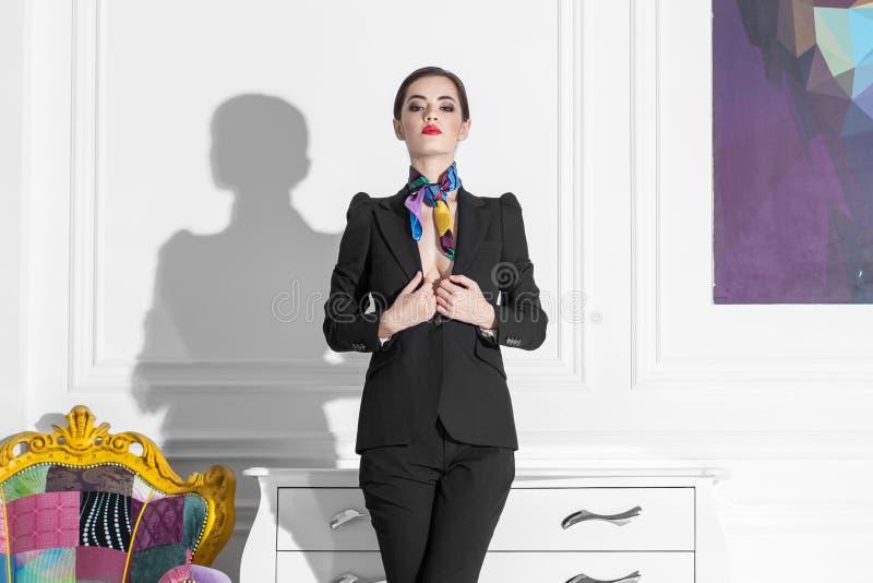 Modelo de moda femenino en el traje que permanece en el arte minimalistic blanco i imagen de archivo libre de regalías