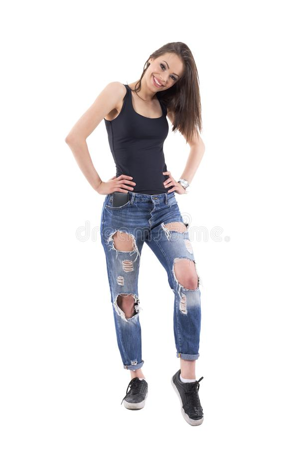 Modelo de moda femenino joven hermoso encantador en los vaqueros rasgados que presentan y que sonríen en la cámara foto de archivo libre de regalías