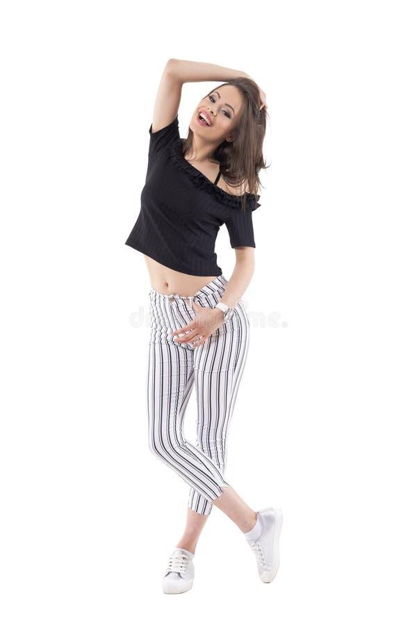 Modelo de moda de moda hermoso imponente de la mujer que presenta con la mano en el pelo que sonríe y que mira la cámara fotos de archivo