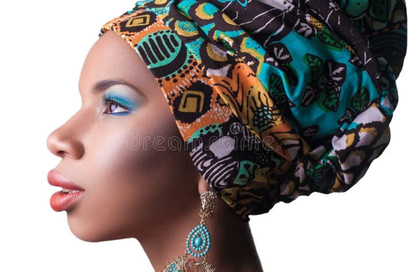 Modelo de moda hermoso joven con estilo africano tradicional con la bufanda, los pendientes y el maquillaje en fondo anaranjado fotos de archivo libres de regalías