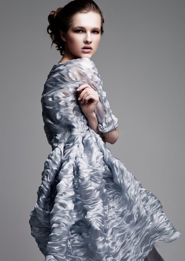 Modelo de moda hermoso que lleva el vestido de seda azul imagen de archivo libre de regalías