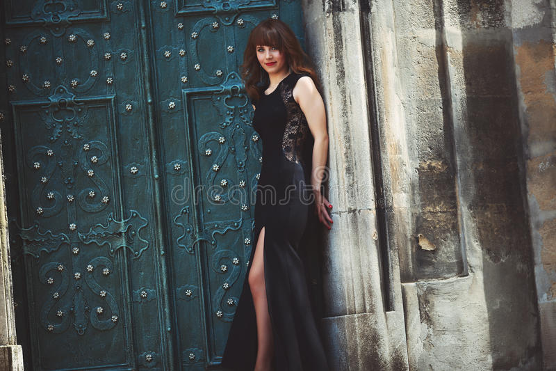 Modelo de moda integral en el vestido negro que presenta en el ne de la calle foto de archivo